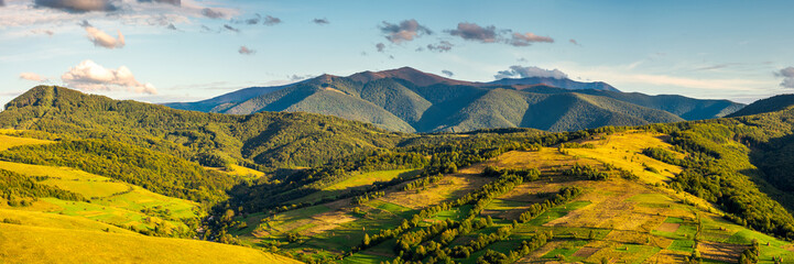 panorama of mountainous rural area in autumn. wonderful countryside with agricultural fields on hills. gorgeous Borzhava ridge in the distance