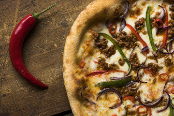 A ground beef pizza with a whole red pepper on the side on a vintage wood surface