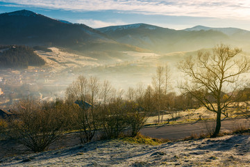 rural valley in autumn at sunrise. beautiful scenery in mountains. road down to village in haze and fog. distant mountain tops in snow