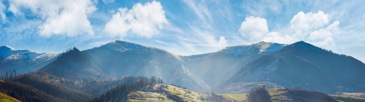 panoramic landscape of mountainous countryside in afternoon. gorgeous cloudscape above the ridge. grassy hills and naked trees. mountain tops in snow