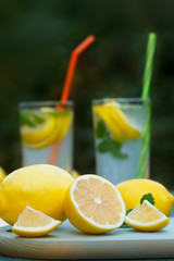 Organic, ripe lemons on blue board. Fresh lemonades or mojito cocktails in two glasses with straws in background.