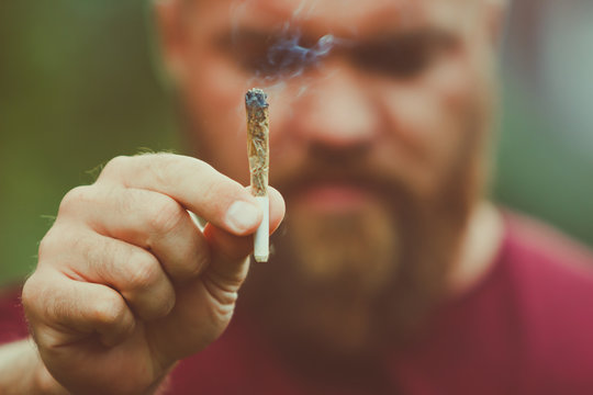 Sad or disappointed young man with beard is holding a smoking marijuana joint - legalization (or legalisation) medical cannabis concept - smoke is coming out of the weed or hashish cigarette
