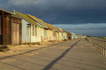 Beach huts with storm clouds