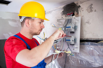 Skilled worker mounting automatic switches on distribution board