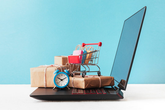 Internet shop / e-commerce sale and delivery service concept: shopping cart multicolored packages and boxes with trolleybus logo on laptop keyboard, blue background