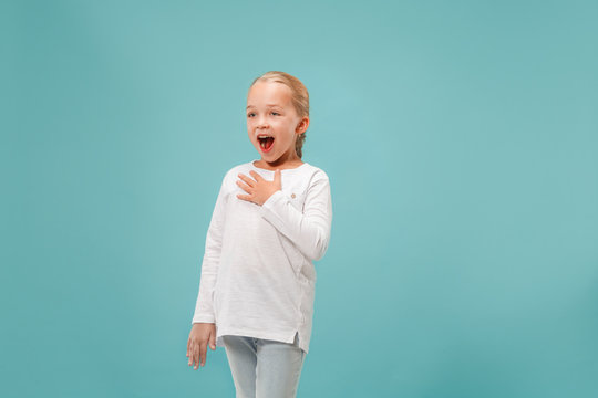 Happy young beautiful girl singing at studio isolated on blue background