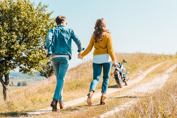 back view of couple walking on rural meadow and motorbike on background
