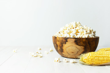 Brown wooden bowl with delicious traditional popcorn on a light wooden background. Top view of a light meal background.
