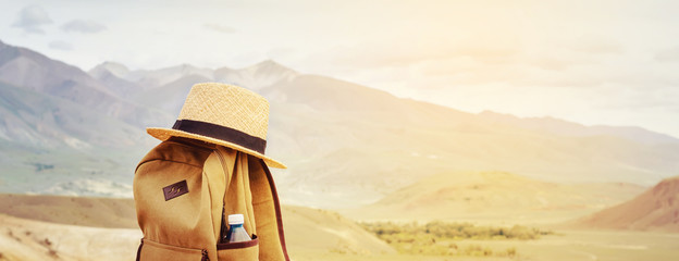 Hipster backpack, bottle of water and straw hat on hill in mountains. Active travel concept.