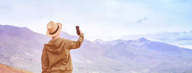 Girl tourist tourist in hat makes panorama of blue mountains on smart phone. Toning sunrise