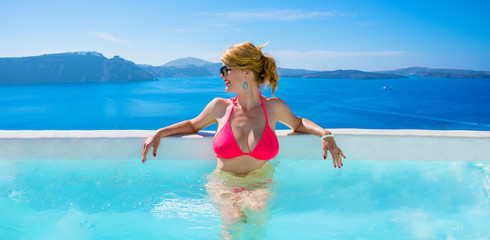 Woman in bikini relaxing in luxury outdoor pool