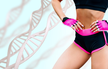 Young woman with athletic body standing among DNA chains.