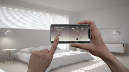 Remote home control system on a digital smart phone tablet. Device with app icons. Interior of minimalist bedroom in the background, architecture design