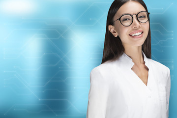 A young woman doctor smiling, standing in front of a blue background with circuit board design. Communicate about health care, medical, technology