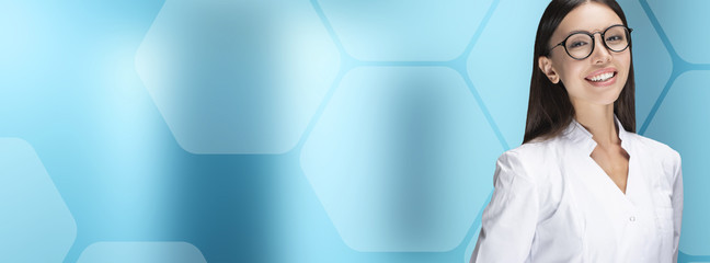 Panoramic, cover concept. A young woman doctor smiling, standing in front of a blue background with hexagons. Communicate about health care, medical, technology