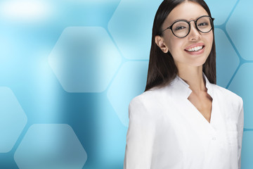 A young woman doctor smiling, standing in front of a blue background with hexagons. Communicate about health care, medical, technology