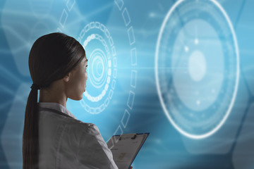 Abstract health care and medical engineering concept. A woman health care professional, or scientist, or bio engineer, is using a futuristic, innovative technology holographic machine