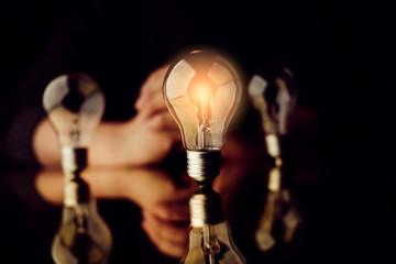 man hand choose glow light bulb creativity business ideas concept black background