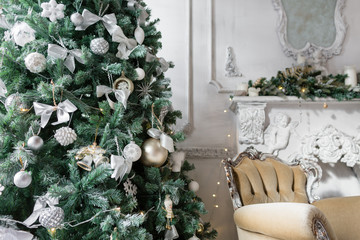 classic apartments with a white fireplace, decorated fir tree, sofa. Christmas morning .