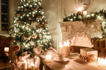 Christmas tree, garlands, candles,lanterns, gifts in the evening. classical interior of a white room with a decorated fireplace, sofa,
