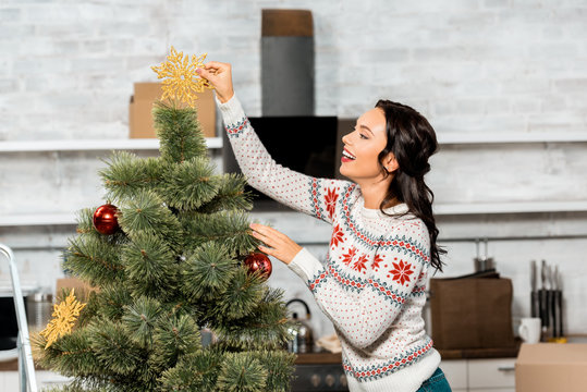 smiling young woman decorating christmas tree by baubles in kitchen at home