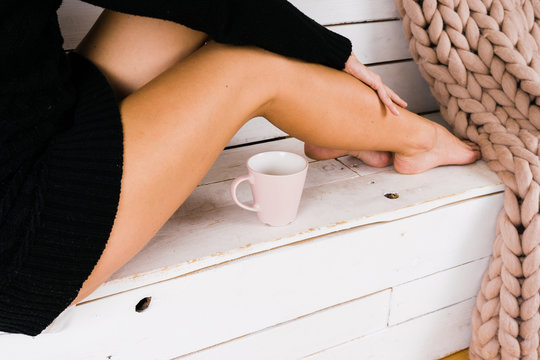 Beautiful young girl in a knitted sweater sits at home and enjoys her hot drink. Model with long and attractive legs rests in its loft. Concept of a dreamy pleasant feeling of warmth in cold season