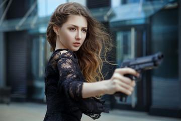 A beautiful elegant girl in an evening dress aims at a  gun.