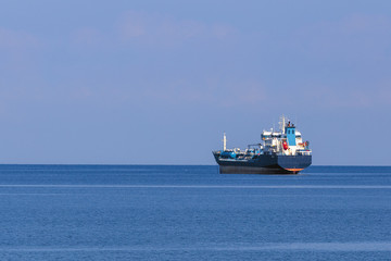 sea cargo ship at sea against  a background of the sea horizon, and a cloudless sky
