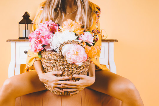 Beautiful girl in a negligee is holding a large basket of flowers. Pastel orange wall. Space for text and logo. Concept of freshness and tenderness of the female body as flowers