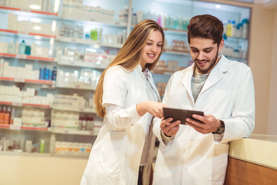 Pharmacists using digital tablet while checking medicine in pharmacy
