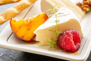 Slice camembert cheese with grilled peach, fresh raspberries and fresh thyme, close up