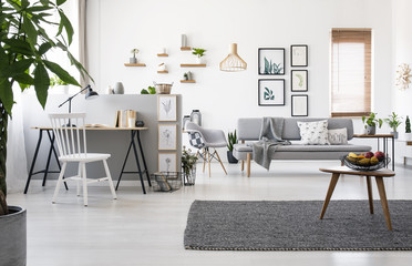 Wooden table on grey carpet in spacious apartment interior with workspace and posters. Real photo