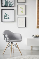 Grey armchair next to cupboard in white living room interior with gallery of posters. Real photo