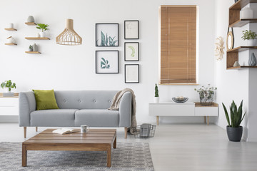 Wooden table in front of grey settee in natural living room interior with blinds and gallery. Real photo