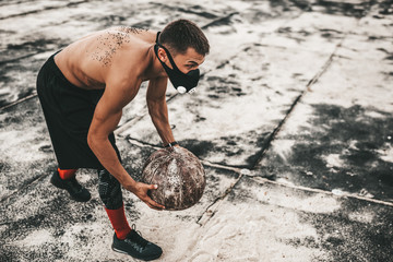 Athelte muscular male doing exercicses with medicine ball in training mask on concrete background outdoor with copy space for your advertising. Caucasian shirtless sportsman doing workout crossfit.