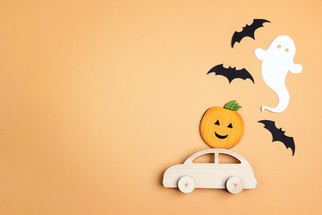 Wooden toy car with funny pumpkin on the roof and bats on orange background. Space for text.