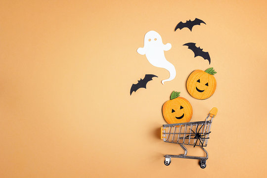 Shopping trolley with decorative pumpkins, ghost, bat and copy space on orange backdrop.  Halloween sale concept.