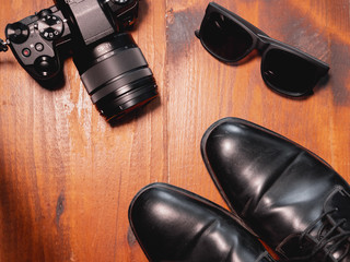 Top view of digital camera with glasse and black shoes on wooden table. Photographer concept