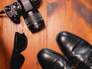 Top view of digital camera with black shoes and sunglasses on wooden table. Photographer concept
