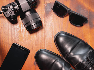 Top view of digital camera, sunglasses with phone and black shoes on wooden table. Travel photographer concept
