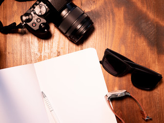 Top view of digital camera, sunglasses, watch and open notebook with pen on wooden table