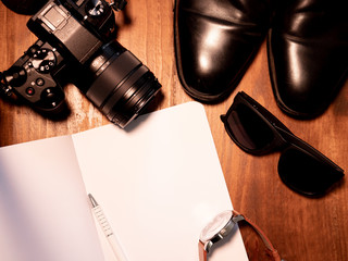 Top view of digital camera, black shoes, sunglasses, watch and open notebook with pen on wooden table. Travel writer photographer concept