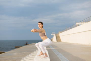 Young pretty woman in sporty top and white leggings doing squats thoughtfully looking in camera while spending time by the sea