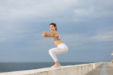Young beautiful woman in sporty top and white leggings doing squats dreamily looking in camera while spending time with sea view on background