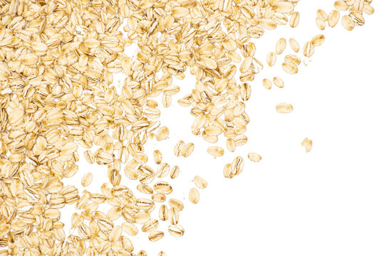 Lot of whole flat raw rolled oats left upper corner isolated on white background