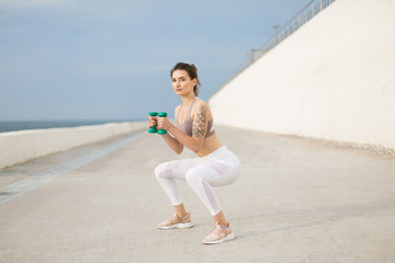 Young beautiful woman in sporty top and white leggings doing squats with dumbbells in hands while thoughtfully looking in camera outdoor