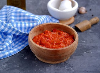 Aivar, vegetable dip or a snack of roasted red sweet peppers and eggplants in a wooden bowl on a dark gray background. Serbian cuisine.
