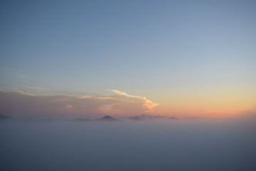 The peak mountain, dense fog cover mountains with background are blue sky, fresh air and mist at dawn