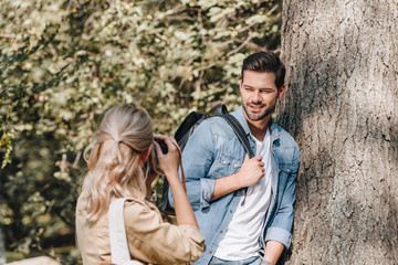 woman taking picture of stylish boyfriend in autumn park
