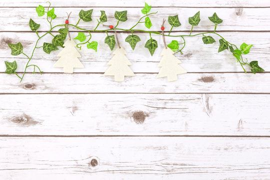 Cute festive Christmas decorations on a vintage whitewash white wood background with space for copy